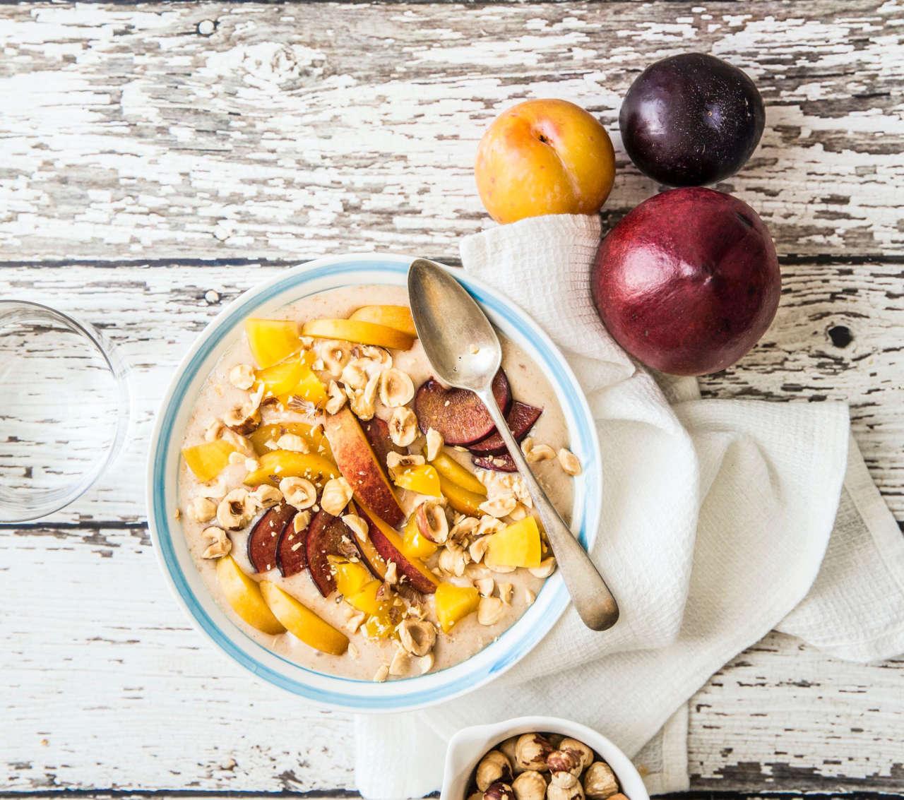 Smoothie bowl vegan di pesche e frutta gialla con nocciole